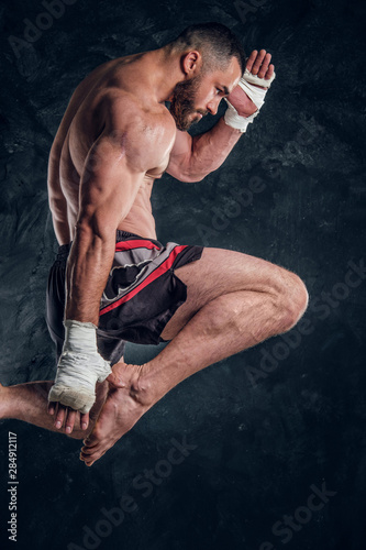 Fotomural Focused physically fit man is jumping, making illusion of flight before punch an dark studio