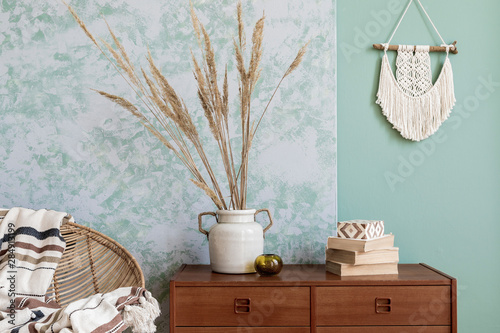 Fotografija  Stylish and boho composition of living room with design armchair, wooden retro commode, books, flowers in vase, beige macrame, plaid and elegant accessories