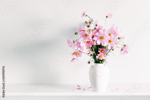 Photo Fresh summer bouquet of pink cosmos flowers in white vase on white wood shelf on white wall background