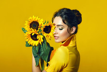 A Girl In A Yellow Dress Holds In Her Hands A Bouquet Of Yellow Sunflowers.