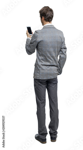Fotografía Back view of a businessman who is looking into the smartphone.