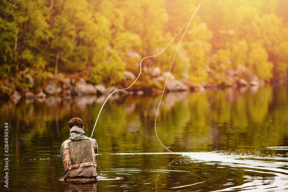 Fototapeta Fisherman using rod fly fishing in mountain river autumn splashing water