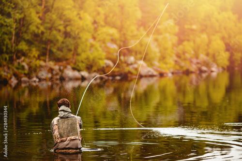 Fisherman using rod fly fishing in mountain river autumn splashing water Fototapet
