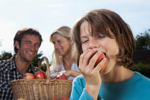 Germany, Munich, Family Eating Apples In Garden