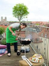 Man Preparing Barbecue On Balc...