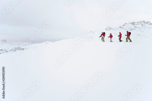Italy,South Tyrol,Four people snowshoeing