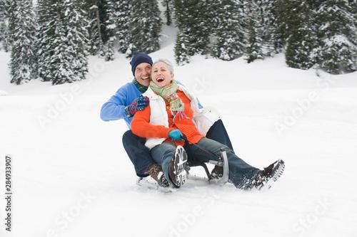 Italy, South Tyrol, Seiseralm, Senior couple sledding down hill, laughing, portrait