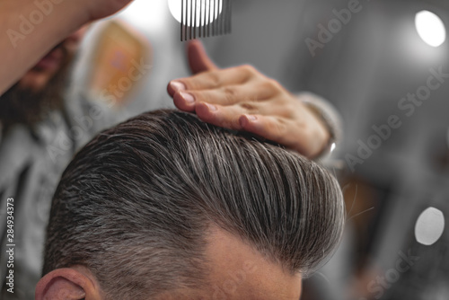 Barber does hair styling. Men's Hair Care. Canvas
