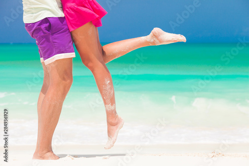 Recess Fitting Gymnastics legs of young kissing couple on tropical turquoise caribbean beach