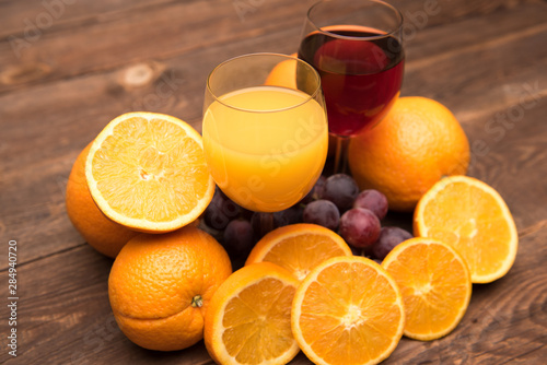 Juice glass and grape and orange fruit on wooden background - 284940720