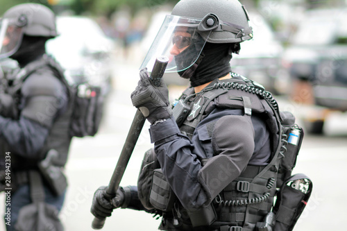 Police officer in riot gear overseeing a crowd of protestors. Fototapet