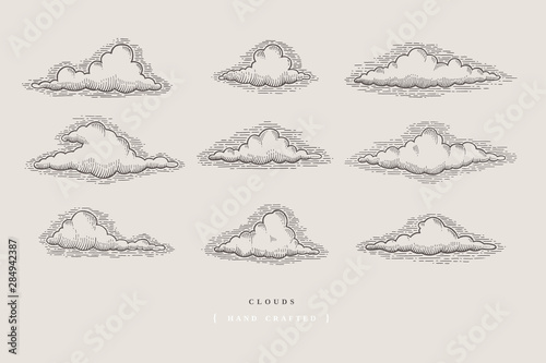 Fototapeta Set of graphically hand drawn clouds on light background. Clouds of various shapes in retro engraving style. Vector vintage illustration. obraz