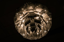 White Pinecone-shaped Chandelier Suspended From The Ceiling And Lit From Within Creates An Abstract Shot.