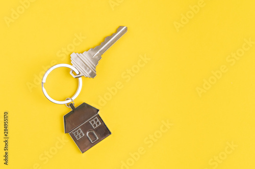 Pinturas sobre lienzo  Home key with house keyring or keychain on solid yellow background using as home