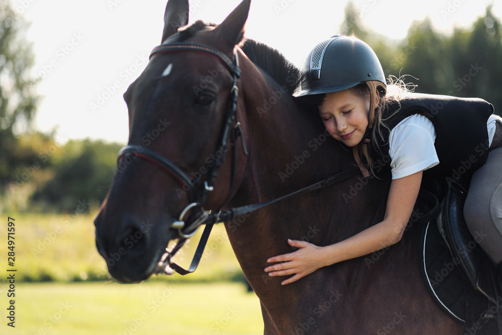 Fototapeta Girl teenager jockey sits on a brown horse, hugs and strokes her.