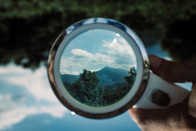 Handheld Loupe Optical Magnification Effects View Upside Down On A Green And Blue Nature Landscape