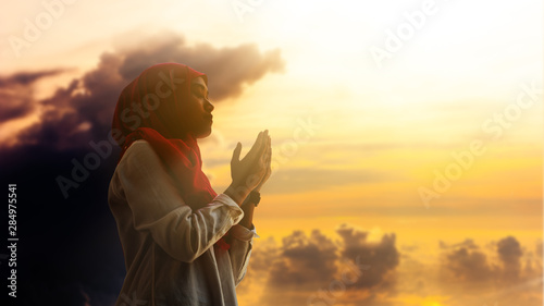 Silhoueitte of young muslim woman pray with beautiful sunset/ sunrise in backgro Wallpaper Mural