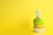 Leinwanddruck Bild - Birthday cupcake with number nine candle on yellow background, space for text