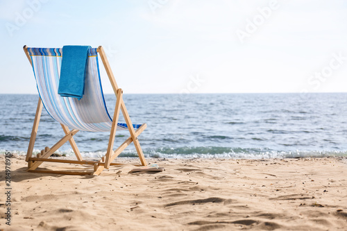 Slika na platnu Lounger and towel on sand near sea, space for text. Beach objects