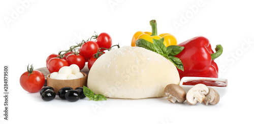 Foto Fresh dough and ingredients for pizza on white background