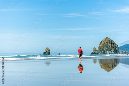 A man in a red T-shirt is walking on the water on the Pacific coast breathing he Canvas Print