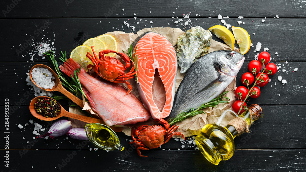 Fototapety, obrazy: Seafood on a black wooden background. Banner Top view. Free space for your text.