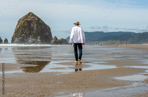 Photo A man in an embroidered shirt and hat walks along the shore of the Northwest Pac
