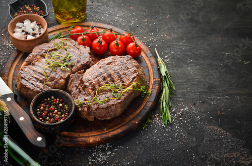 Grilled ribeye beef steak, herbs and spices on a dark table Fototapet