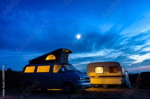 Carta da parati A camper van with its pop top roof open parked next to a vintage caravan in a campsite at nightfall, both illuminated from inside and the moon glowing above in a stormy sky