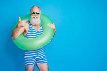 Portrait Of Cheerful Grandfather In Eyewear Eyeglasses Showing Approval Sign Wearing Striped Bathing Suit Isolated Over Blue Background