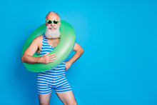 Portrait Of Cheerful Granddad With Eyeglasses Eyewear Holding Life Belt On His Shoulder Wearing Striped Swim Wear Isolated Over Blue Background