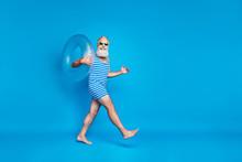 Full Size Profile Size Photo Of Cheerful Man With Eyeglasses Eyewear Holding Toy Ring On His Shoulder Walking Wearing Swim Wear Isolated Over Blue Background