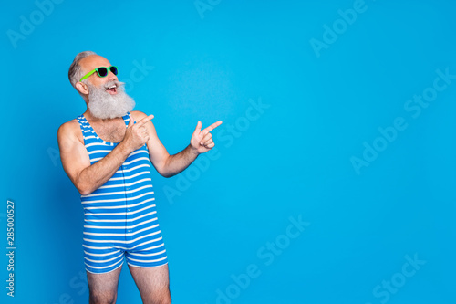 Fototapeta Portrait of his he nice attractive confident cheerful cheery glad gray-haired man pointing ad advert sale discount black Friday copy space isolated on bright vivid shine blue background obraz