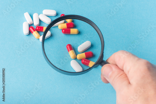 Cuadros en Lienzo  Concept - pharmaceutical testing, testing of medicines, magnifying glass, tablets on a blue background