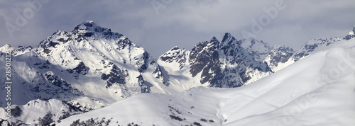 Foto auf Leinwand Dunkelgrau Snowy off-piste slope and mountains in clouds