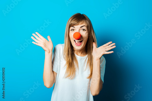 Beautiful young woman in a white T-shirt and a red clown nose smiles and makes hand gestures on a blue background Wallpaper Mural