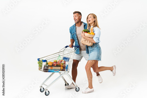 Photo of joyful family woman and man holding food products in supermarket and carrying shopping cart isolated over white background