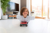 Boy with arms open lying on skateboard at home - 285029177