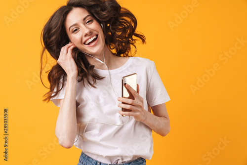 Emotional smiling young woman posing isolated over yellow wall background listening music with earphones dancing using phone. - 285035508
