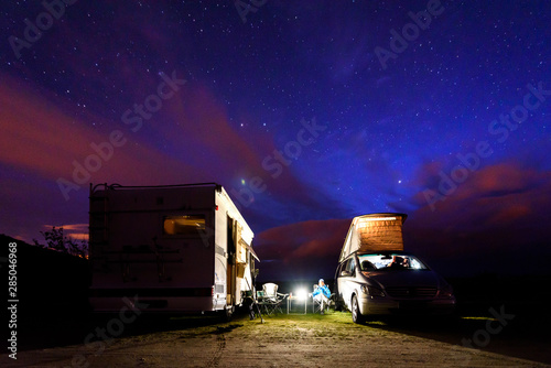 Fotografie, Obraz  Campervans are parked on a beach at night under stars.