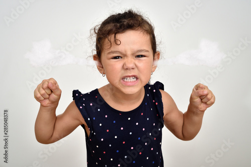 Obraz Angry and aggressive young girl with clenched teeth and fists and steam blowing out of her ears looking at the camera - fototapety do salonu
