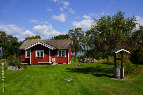 Traditional Swedish cottage in the countryside against a partly clouded blue sky Fototapeta