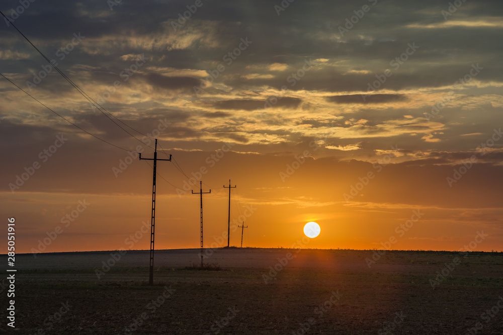 Sunset behind the horizon and electric poles in the field