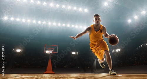 Professional basketball player dribbling. Floodlit sports arena