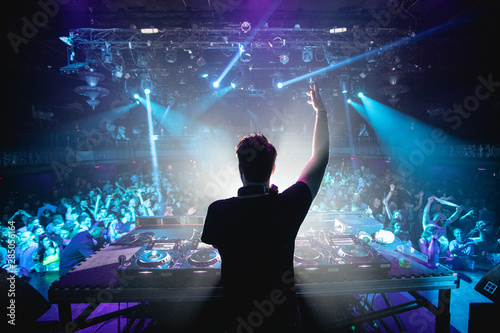 Foto  Silhouette of DJ in nightclub with hands up, shot from behind