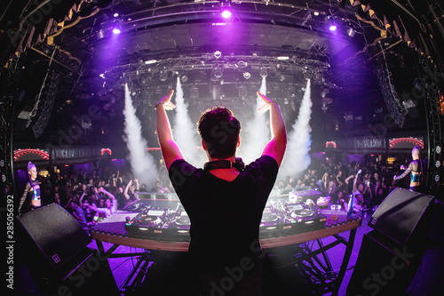DJ in nightclub with hands up and cryo canons, shot from behind Canvas Print