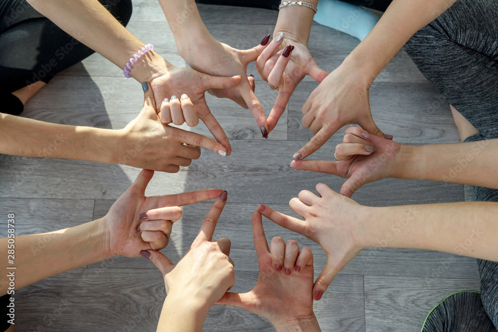 Fototapeta Circle of human hands doing yoga exercises close up