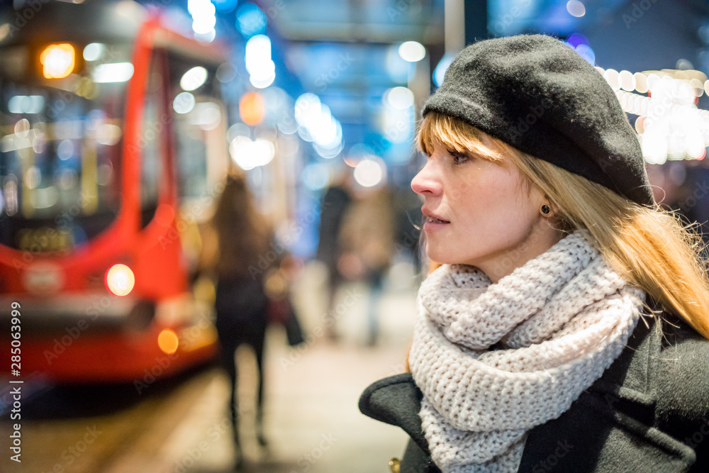 Fototapety, obrazy: Young woman in the night city waiting at bus stop