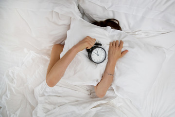 Unrecognizable woman in bed, covering her head with a pillow. She doesn't want to wake up.