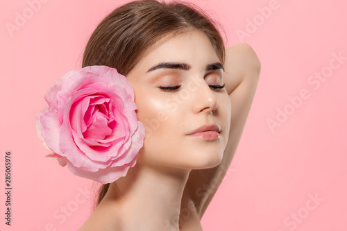 Close-up portrait of a beautiful young girl with pink rose flower isolated over pink background.